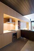 Moderne Einbauküche aus hellem Holz und dunkle Holzdecke