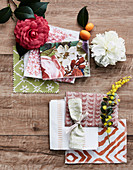 Fabric samples, flowers and kumquats on a wooden background