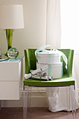 Two white hatboxes and Christmas crackers on green chair
