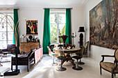 Runder Holztisch mit Klassikerstühlen vor großformatigem Gemälde, Ledergarnitur und Holzkommode im Wohnzimmer