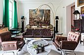 Braune Ledergarnitur und italienische Designerleuchte im Wohnzimmer, im Hintergrund großformatiges Gemälde