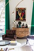 Gemälde über Holzkommode, im Vordergrund Couchtisch und Ledersessel im Wohnzimmer