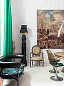 Black leather couch, table lamp on pillar, chair and painting in dining area with classic chairs