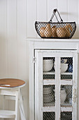 Wire basket on top of small cupboard with wire door panels holding crockery