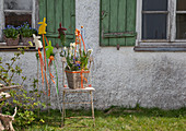 Easter arrangement in basket and Easter-themed garden stakes outside house