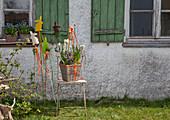Österliches Gesteck im Korb und Osterstecker vor dem Haus
