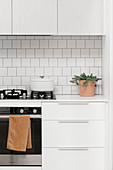 Gas stove in a simple, white kitchen