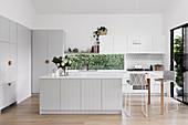Moderne Landhausküche in Hellgrau mit horizontalem Fenster