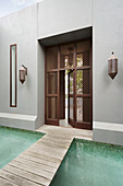 Footbridge across the pool to the house with a Moroccan style lattice door