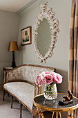 Pink roses in glass vase on round occasional table, in the background is an antique settee beneath a plaster framed mirror