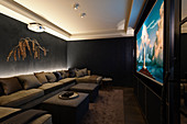Chic home cinema in dark tones and extended sofa seating