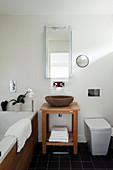 Stone washbasin on wooden washstand in bathroom with slate floor tiles