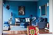 Blaues Wohnzimmer mit verschiedenen Sitzmöbeln, Liege und Kunstwerk an der Wand