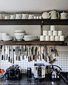 White crockery on open shelving above kitchen work top with knife rack, toaster and kettle