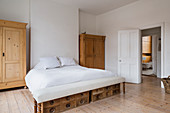 Large white bed in minimal white bedroom with wooden wardrobes and flooring