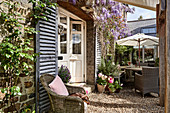 Vintage French shutters and wicker armchairs on terrace