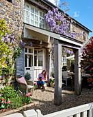 Natursteinhaus mit Glyzinen bewachsen, Frau mit Hund beim Eingang