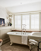 Free-standing bathtub below window with closed shutters and oil painting on ledge