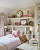 Shelves of toys and large clock above bed in girl's room