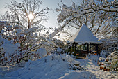 Snow-covered pavilion in wintry garden