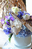 Summery flower arrangement of driftwood and blue and white flowers