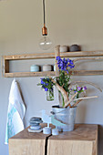 Driftwood arranged in zinc bucket and decorated with summer flowers in glass vases
