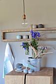 Treibhölzer arrangiert im Zinkeimer dekoriert mit Sommerblumen in Glasvasen