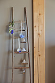 Handcrafted wooden ladder holding flower arrangements and garland of paper boats