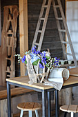 Summer flowers in zinc bucket enclosed in pieces of driftwood and hessian ribbon