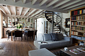 Grey sofa set and bookcase in front of spiral staircase in open-plan interior with dining area in background