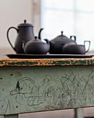 Black, 1920s basalt tea service on rustic table