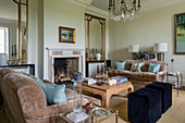 Large antique mirrors in airy sitting room with fireplace and pair of sofas upholstered in taupe linen velvet