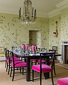Wallpaper in dining room with French crystal chandelier and dining chairs upholstered in velvet