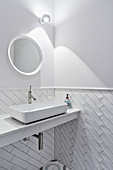 White bathroom with walls tiled to half height with subway tiles