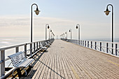 Ocean pier with balustrade, street lamps and benches below blue sky
