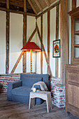 Stool, grey armchair and standard lamp in seating area in timber-framed house