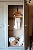 Top on coat hanger and cushions in old wooden wardrobe