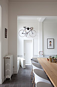 Bicycle hung on wall in hallway and open-plan dining area in period building