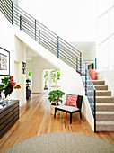 Bright hallway with wooden floor under the stairs with metal railings