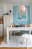 White table and stools in front of pale blue wall in open-plan kitchen
