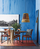Dining table with leather chairs in the room with blue walls
