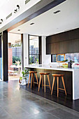 Kitchen island with bar stools in front of a patio door in an elegant kitchen in an open space