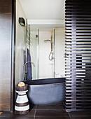 Freestanding bathtub behind a room divider