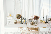 Autumnal arrangement of hydrangeas, pumpkins and candlesticks on table