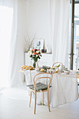 Table set for Easter breakfast in dining room decorated entirely in white