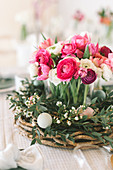 Flower arrangement of wicker wreath, tulips and ranunculus