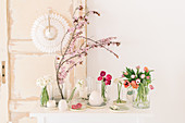 Ranunculus, tulips and flowering branches in glass vases on Easter table