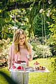 Woman stood next to cakes on DIY suspended table in garden
