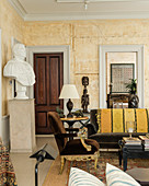 Brown velvet armchair in living room with large plaster bust on plinth and African Mende carvings