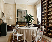 English china on ceiling height shelves in dining room with white american 19c chairs, artwork and rug